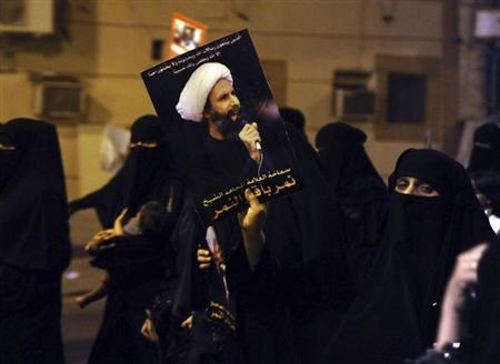 A protester holds up a picture of Sheikh Nimr during a rally in Qatif, against Sheikh Nimr's arrest
