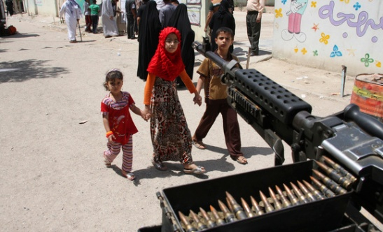 Children walk by a machine-gun near election centre in Baghdad
